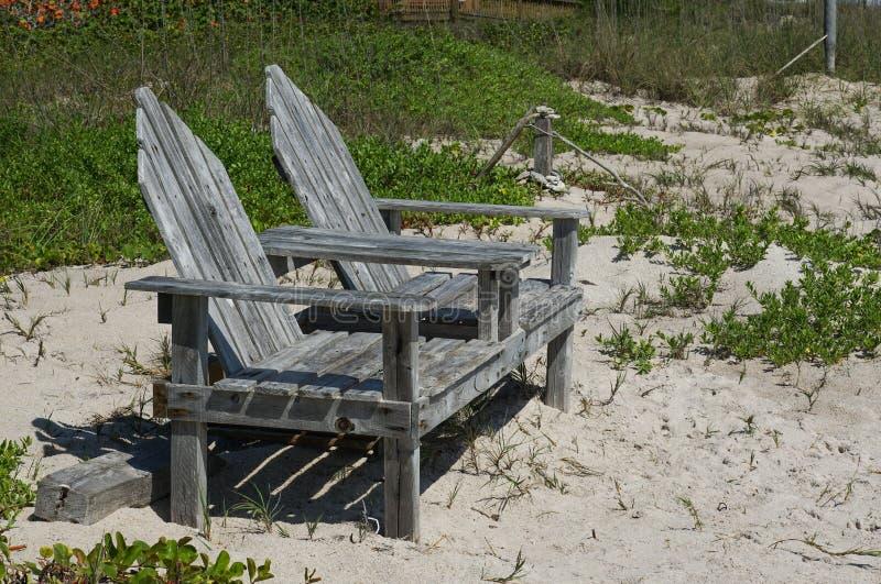 Beach chairs sitting desolate on a sandy beach stock photo