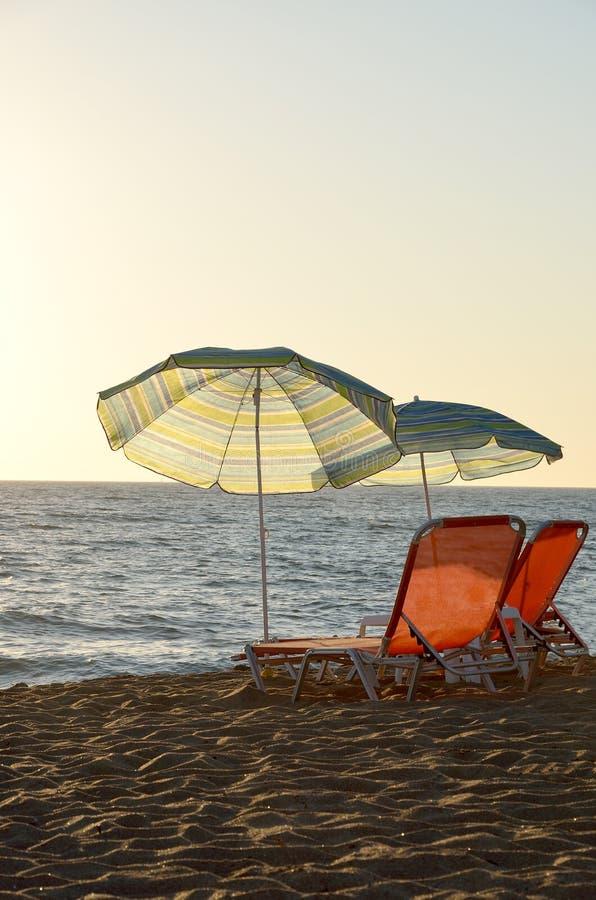 Beach chairs and umbrellas on the beach. Beach chairs and umbrellas on sandy beach in sunset time stock photography