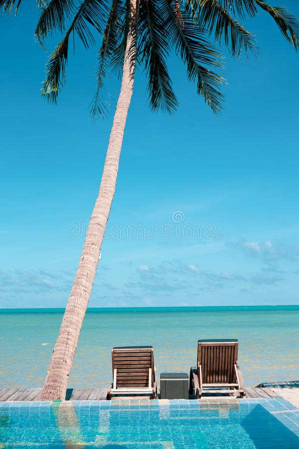 Beach chairs under coconut palm near the sea vacation concept. royalty free stock photos