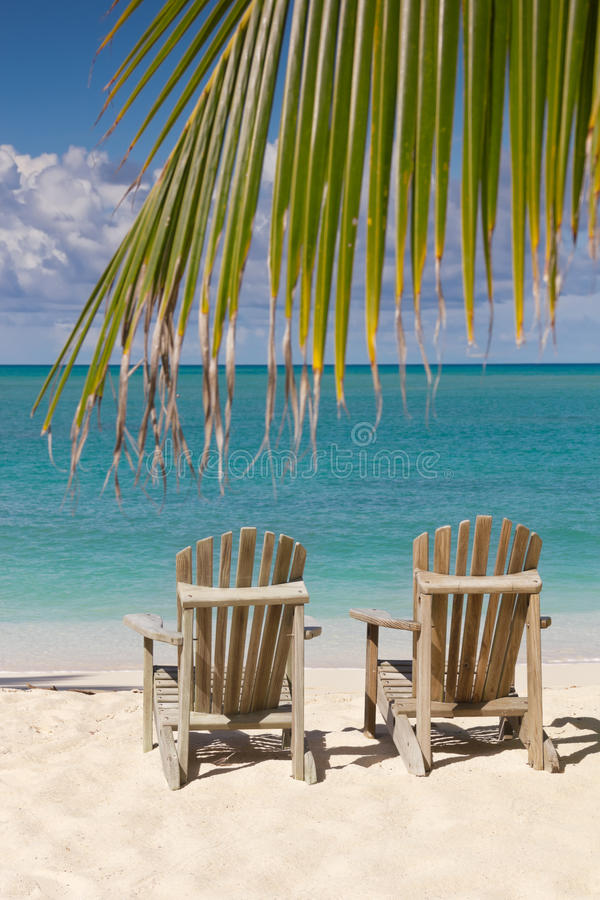 Beach chairs on white sand with blue sky. Beach chairs on white sand beach with cloudy blue sky, sun, and palm tree branch stock photo