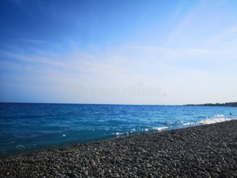 Turquoise sea beach in Nice, France, France. Beach in the city of Nice, in France. Cote d Azur, France. Light blue or turquoise water of Nice beach in France stock photography