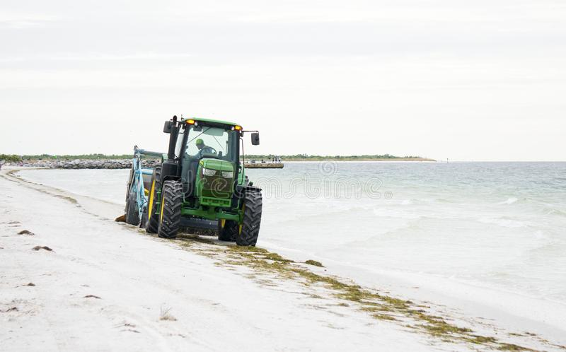 Beach cleaner on the Gulf of Mexico at St. Pete Beach, Florida. St. Pete Beach, Florida, October 23, 2018: A tractor pulling a beach cleaning machine moves stock images