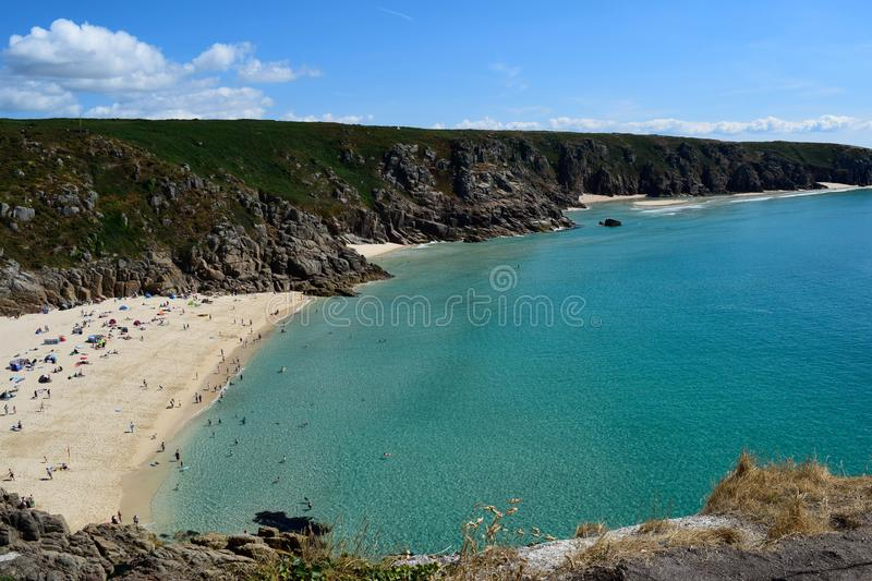 Beach and cliffs, Porthcurno, UK. A view from the cliffs at Porthcurno beach, Cornwall, UK. Pictured on a summers day. bathe bathing bay blue clear clouds cool stock photo