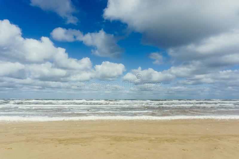 Beach with cloudy blue sky and waves at the sea background royalty free stock image