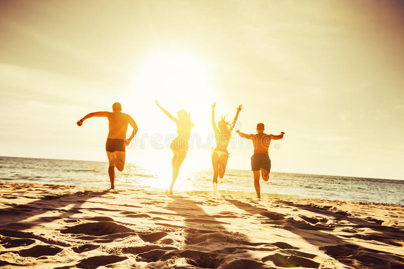 Beach concept group four friends. Silhouettes of four friends runs at sunset beach to the sea royalty free stock photo