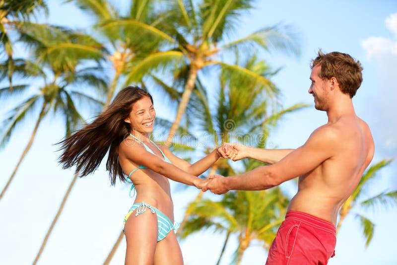Beach couple fun on vacation dancing playful stock image