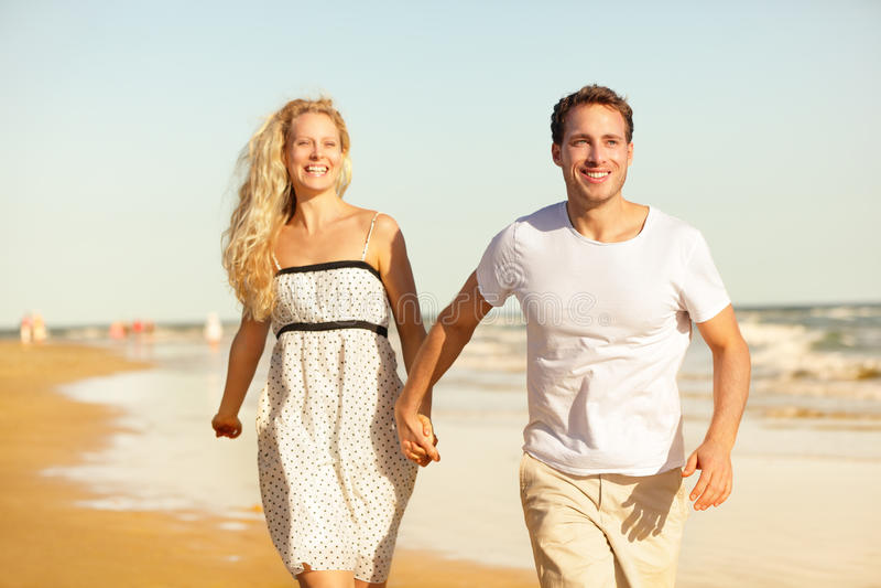 Beach couple holding hands running having fun stock image