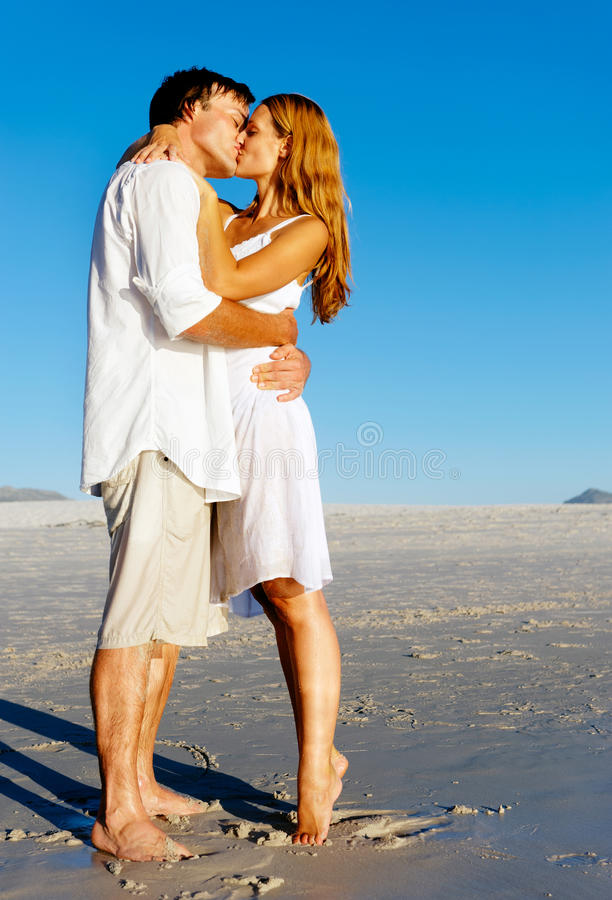Beach couple kiss. Couple in love stand on the beach in summer and share a kiss at sunset alone and on honeymoon royalty free stock image