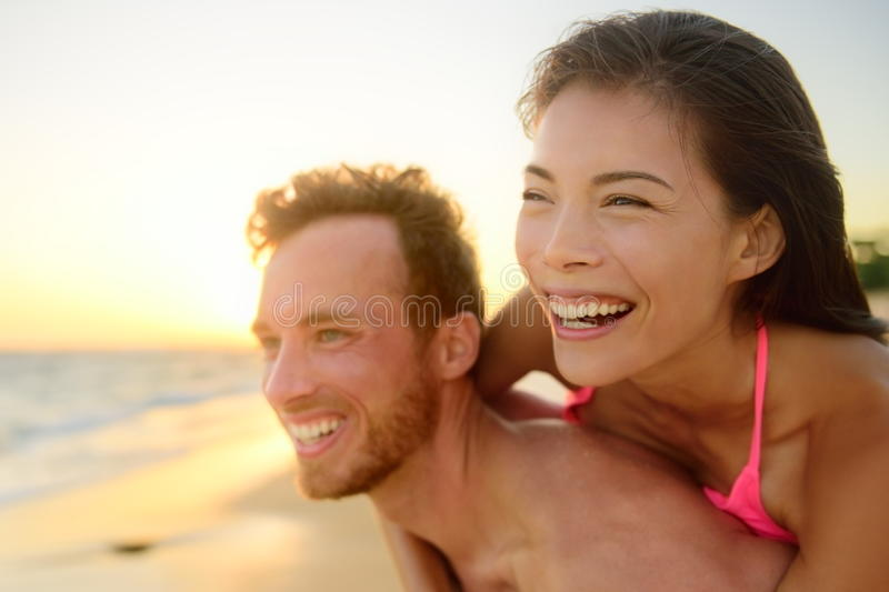 Beach couple laughing in love having fun romance stock photo