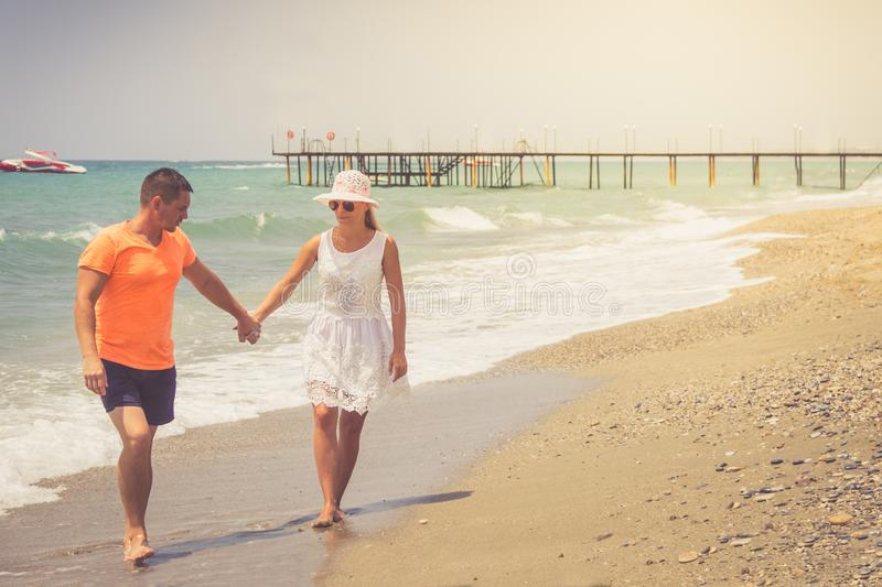 Beach couple walking on romantic travel honeymoon vacation summer holidays romance. Young happy lovers, Caucasian woman and man ho. Beach couple walking on stock image