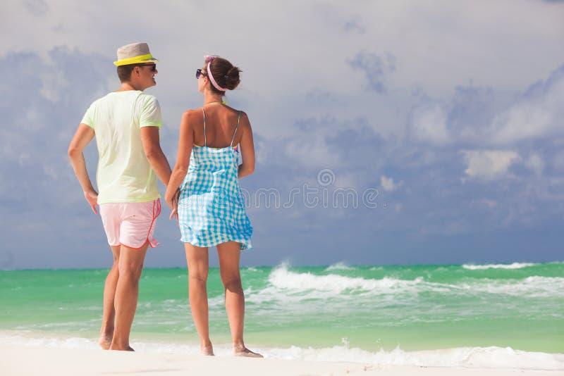 Beach couple walking on romantic travel honeymoon vacation summer holidays romance. Young happy lovers, Cayo LArgo, Cuba royalty free stock image