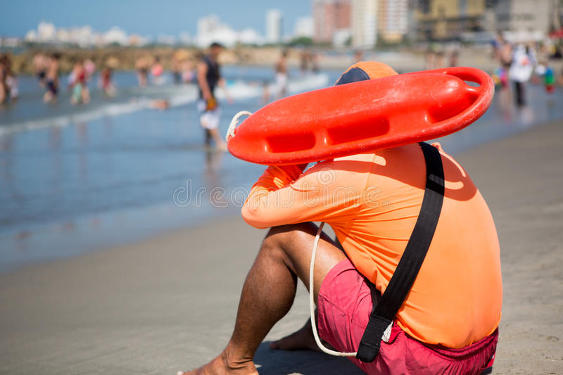 Beach Dealer walking on the beach. Young man life saver watching the situation on the sea in Bocagrande Beach in Cartagena, Colombia 2014 royalty free stock image