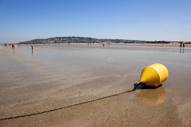 Beach of Deauville. At the beach of Deauville, low tide, yellow buoy in foreground stock photo