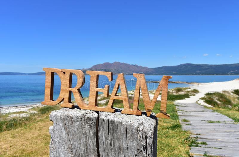Beach with Dream wooden sign. Galicia, Spain, sunny day. stock photography