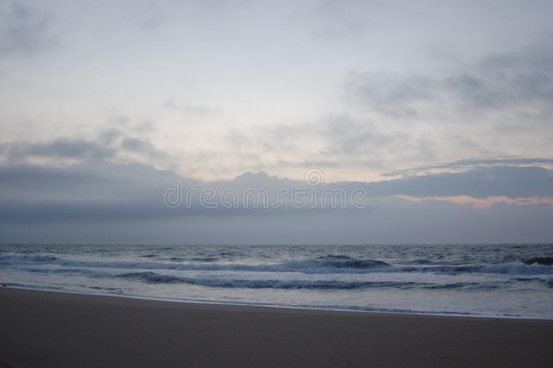 Sunrise on the ocean, white sky, and sand royalty free stock photography
