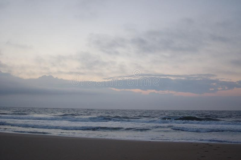 Sunrise on the ocean, white sky, and sand royalty free stock images