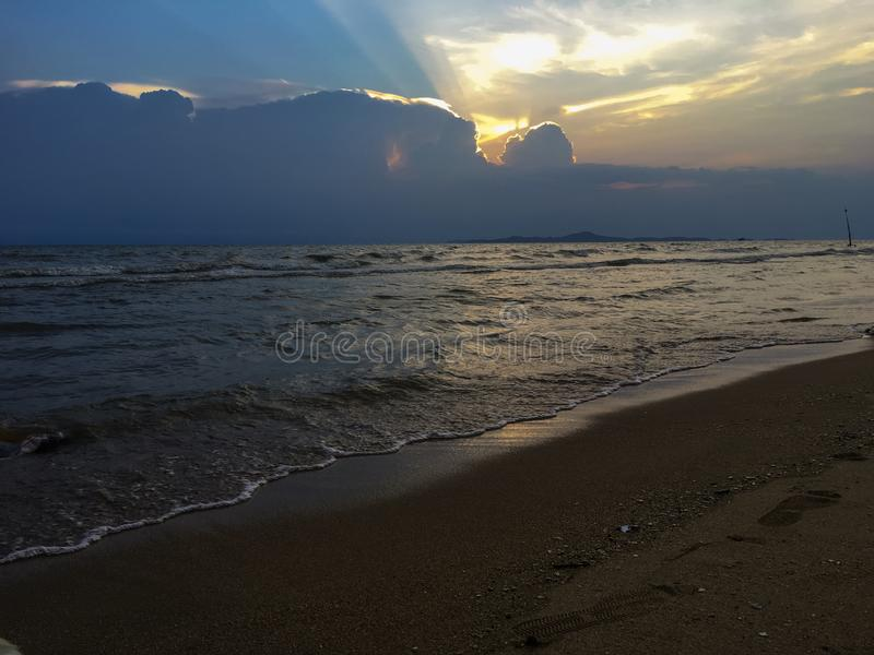 The beach at the end of the day, the sun is falling, the big cliffs obscure the sun like a storm that is approaching. royalty free stock photography