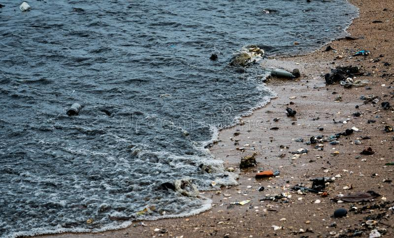 Beach environment pollution. Oil stains on the beach. Oil leak to the sea. Dirty water in the ocean. Water pollution. Harmful royalty free stock image