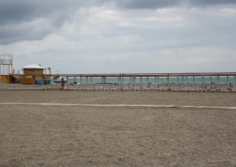 Beach is equipped with chaise-longues and lifeguard post. Beach with chaise-longues and lifeguard post stock photos