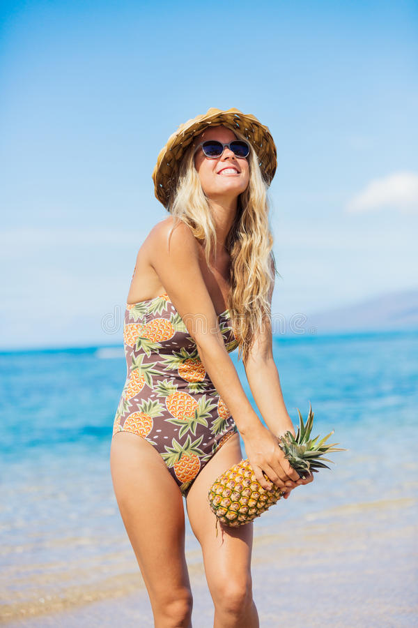 Beach fashion concept. Fun retro beach fashion concept. Woman in pineapple bathing suit and sun hat at the beach stock images