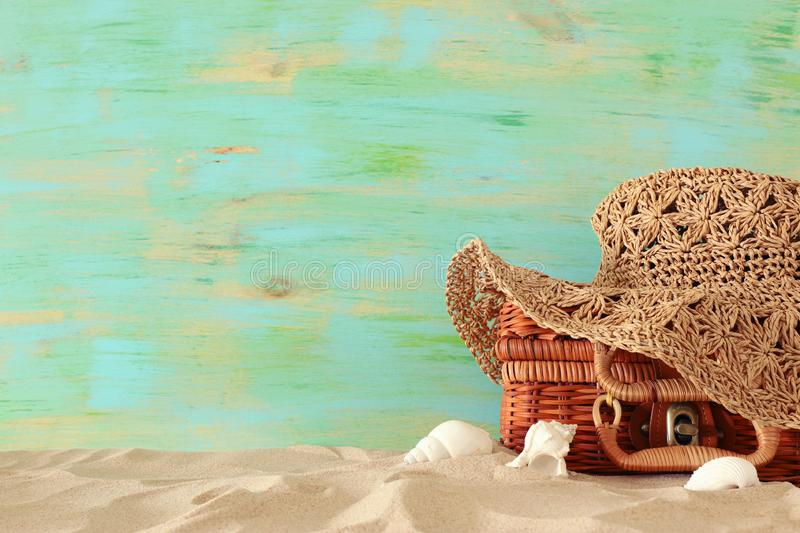 Beach fashion female hat over straw suitcase in the sand. Tropical summer vacation concept stock photography