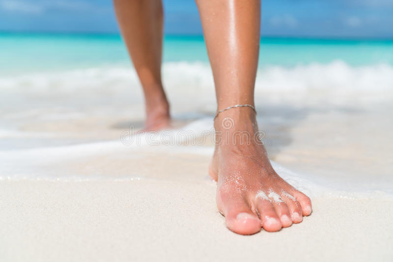 Beach feet closeup - woman walking in water waves royalty free stock photo