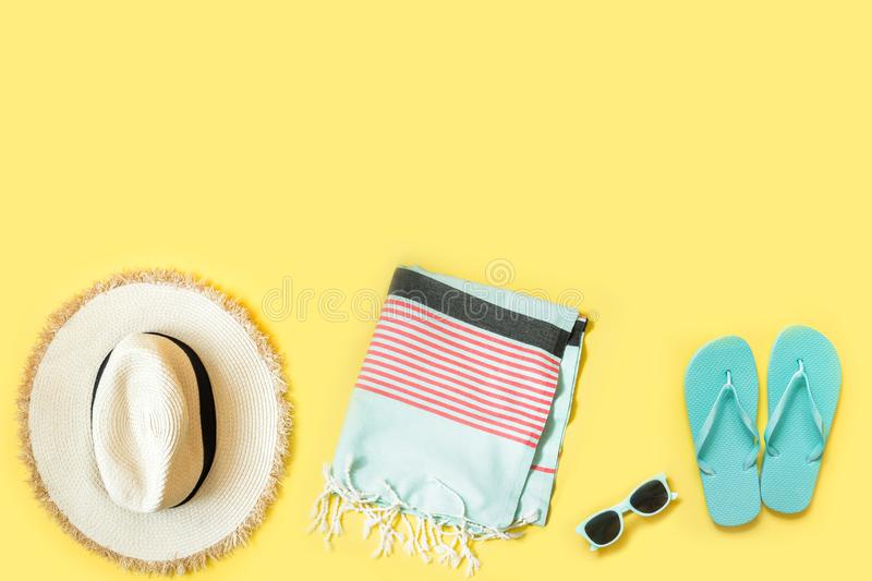 Beach female accessories, straw beach hat, towel, sunglasses on yellow. Space for text. Summer tropical vacation. Beach female accessories, straw beach hat stock photo