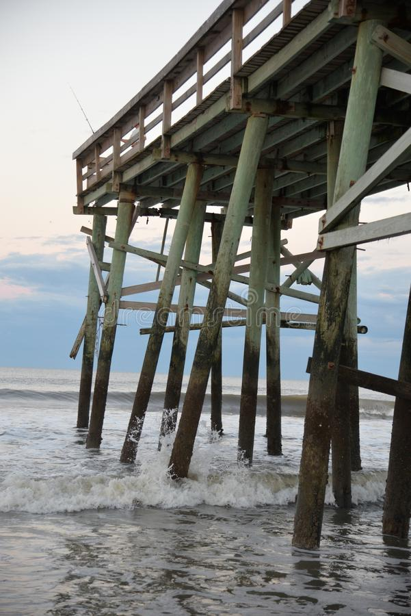 The beach fishing pier is a wonderful structure built to withstand the brutal weather often associated with the beachfront. The fishing pier is an ideal photo royalty free stock images