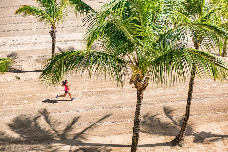 Beach fitness active woman runner running on sand beach from above with palm trees background. Healthy cardio workout athlete royalty free stock photo