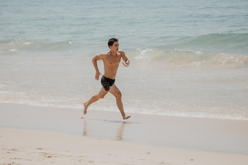 Beach fitness man runner running training cardio. Healthy lifestyle male athlete doing exercise living an active life working out. Beach fitness man runner stock image