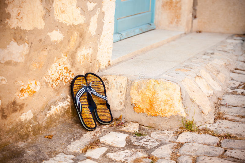 Beach flip-flops on the old wall background stock photo