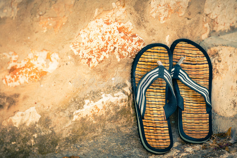 Beach flip-flops on the old wall background. Horizontal shot stock photo