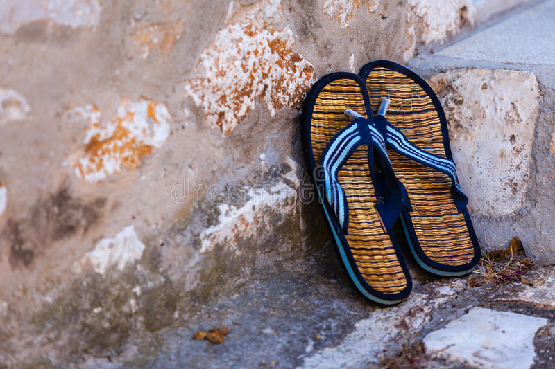 Beach flip-flops on the old wall background stock photography