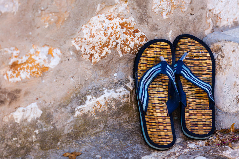 Beach flip-flops on the old wall background. Horizontal shot royalty free stock image