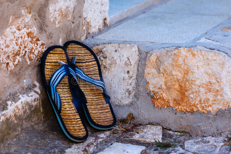 Beach flip-flops on the old wall background royalty free stock photos