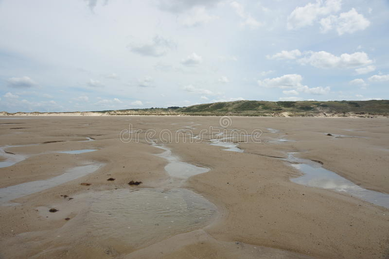 Beach in France. A generic wet beach in france with some dunes in the distance royalty free stock photos