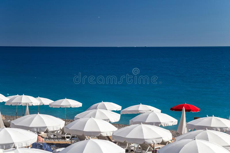 Beach on French Riviera. Beach in French Riviera. White sunbeds and umbrellas in the background of turquoise sea. Nice, Cote d`Azur royalty free stock photos