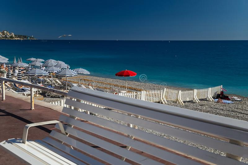 Beach on French Riviera. Beach in French Riviera. White sunbeds and umbrellas in the background of turquoise sea. Nice, Cote d`Azur royalty free stock image