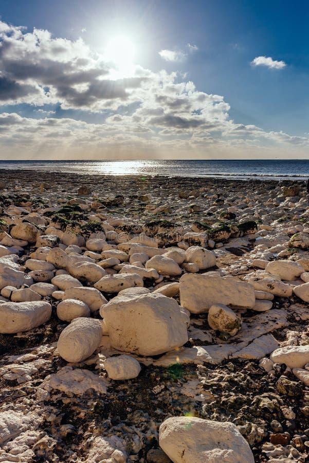 Calm beach full of rocks stock photography