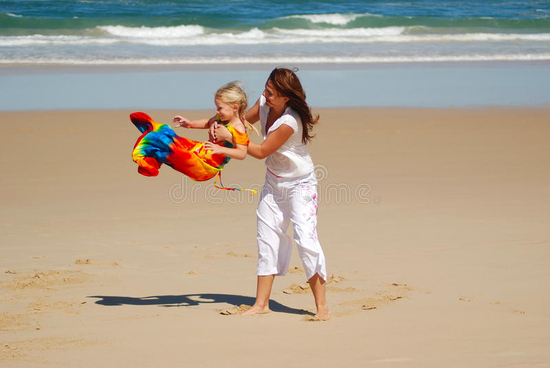 Beach fun with mom. A beautiful young Caucasian woman playing with her little daughter on the beach during summer holidays stock photography