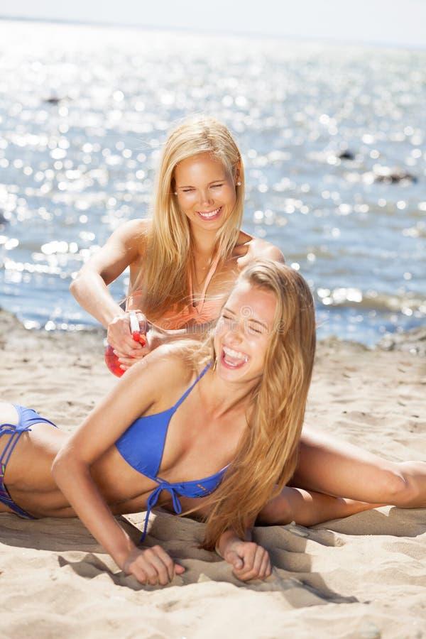 Beach fun. Two girls having fun on the beach royalty free stock images