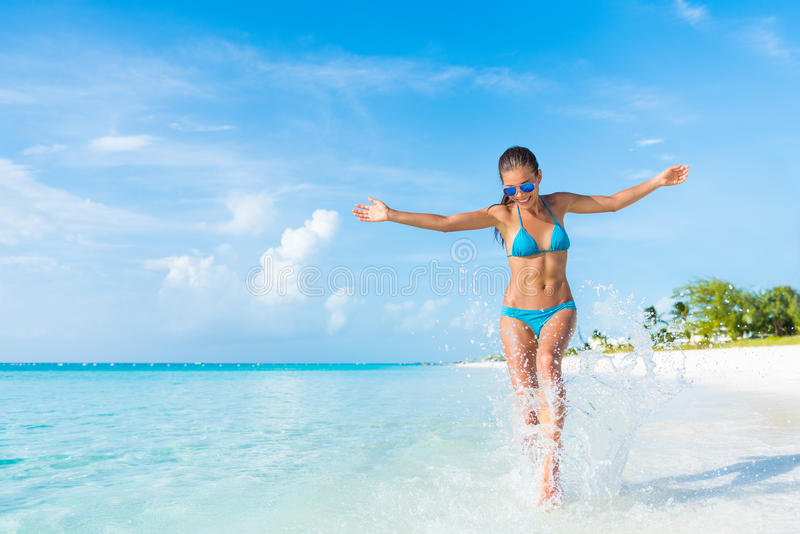 Beach fun vacation carefree woman splashing water. Freedom carefree girl playing splashing water having fun on tropical beach vacation getaway travel holiday stock image