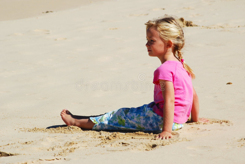 Beach girl little. A cute little blond caucasian girl sitting in the sand at the beach and staring royalty free stock photos