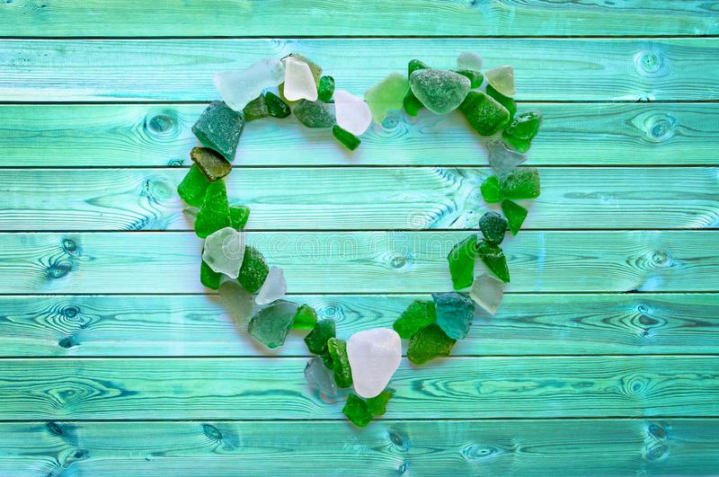 Beach glass collection in the shape of a heart on blue planks royalty free stock photos