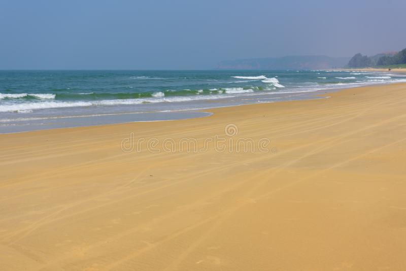 Beach in Goa, India. Sea waves and bright yellow sand stock photo