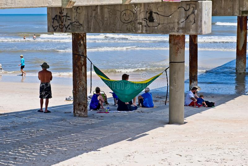Beach goers hangout underneath a concrete pier at St. Augustine Beach, Florida usa royalty free stock photography
