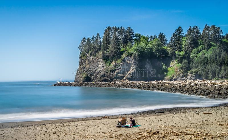 Small Islands Off The NW Coast Of The United States. Beach goers soak in the sun in front of sea stacks royalty free stock image