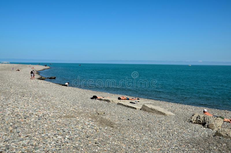 Beach goers sunbathe and relax at rocky Black Sea shore coastline Batumi Georgia royalty free stock images