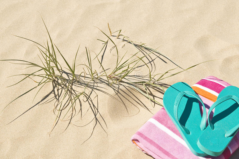 Beach grass towel and flip-flops. Towel flip-flops/thongs on the sand with beach grass stock photography