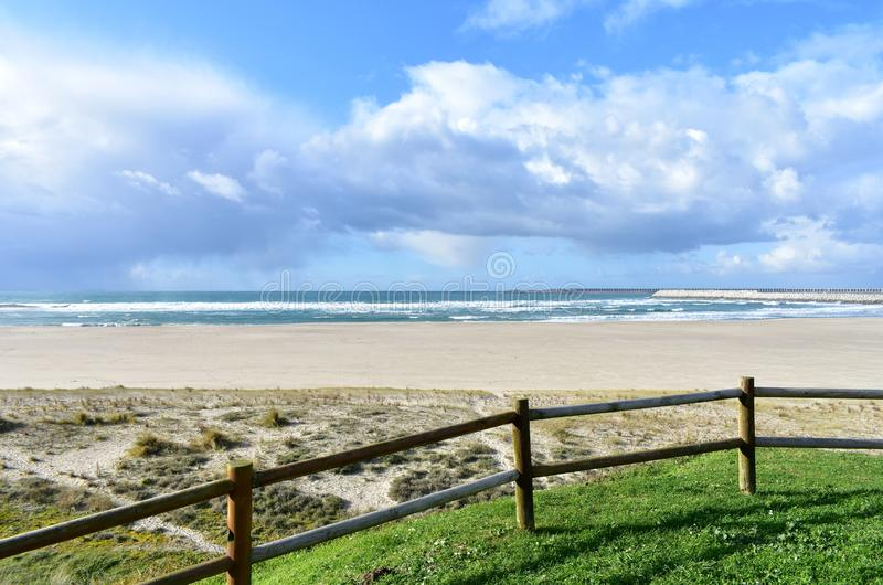 Beach with grass, wooden fence and industrial port. Sea with waves and cloudy sky, Sabon, Spain. royalty free stock image
